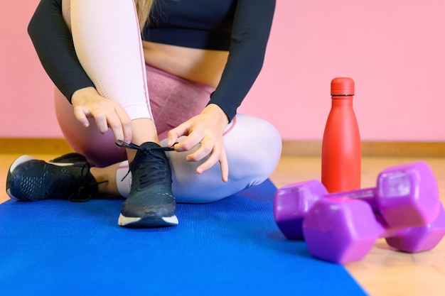 Close up of woman tying laces of training shoes before exercise.