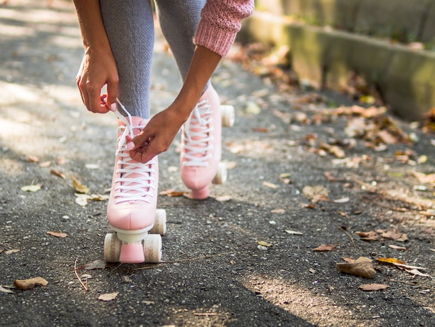 Close-up of woman tying shoelace on roller skate with copy space