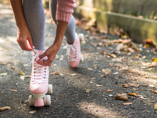 Close-up of woman tying shoelace on roller skate with leaves