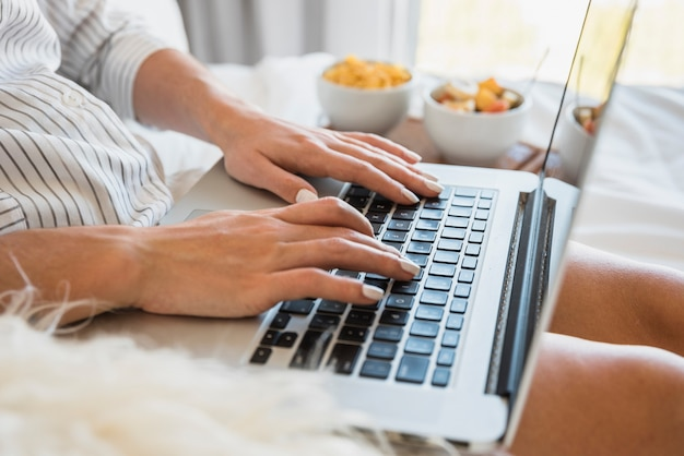 Close-up of woman typing on laptop with breakfast on bed