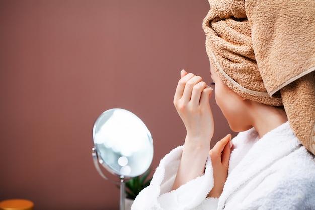 クローズアップ女性は液体のクリームを使用して顔の皮膚の世話をする