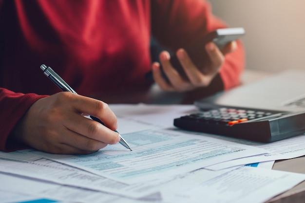 Крупным планом женщина, использующая ручку для заполнения формы индивидуальной налоговой декларации