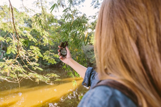 Close-up of a woman using compass for direction in forest