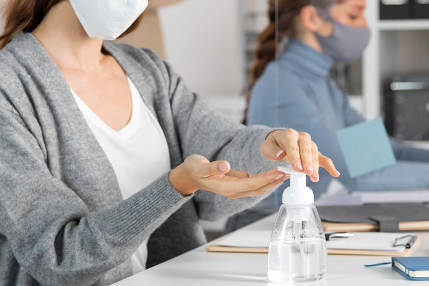 Close-up woman using disinfectant