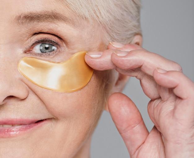 Крупным планом женщина с помощью повязки на глаз