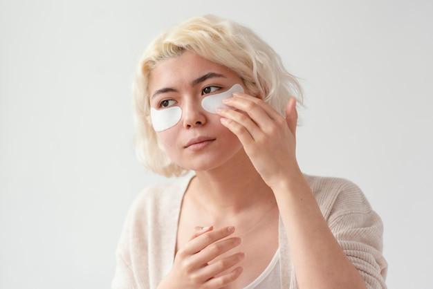 Крупным планом женщина, используя повязки для глаз