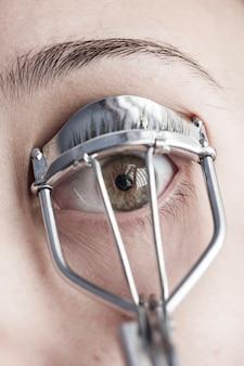 Close-up of woman using an eyelash curler