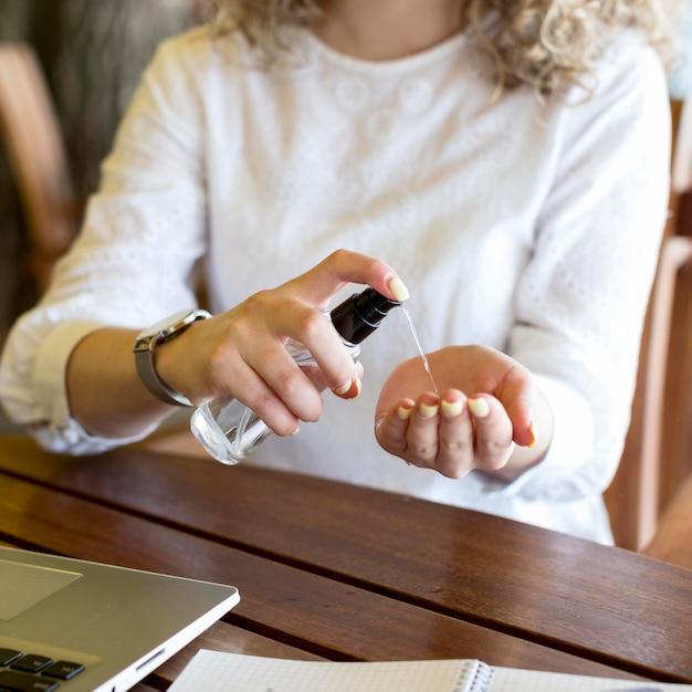 Крупным планом женщина, использующая дезинфицирующее средство для рук