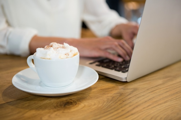 Close-up of woman using laptop by coffee with froth on table in cafe