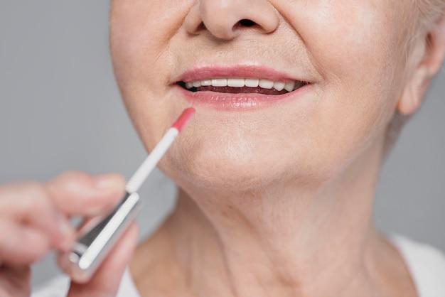 Крупным планом женщина, использующая блеск для губ