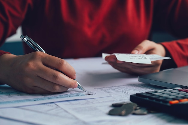 Close up woman using a pen filling form of individual income tax return in living room at home
