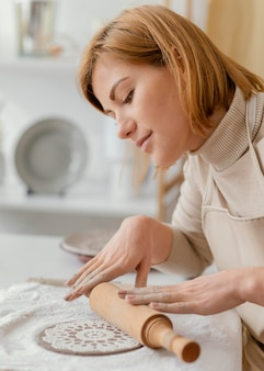 Donna del primo piano usando il mattarello per ceramiche