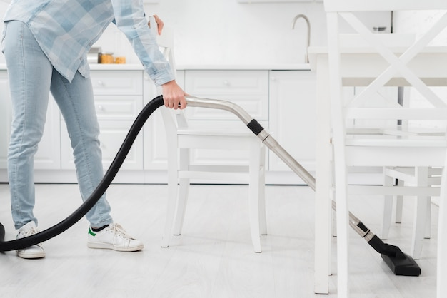 Close-up woman using vacuum to clean