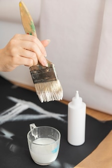 Close-up woman using white paint and brush