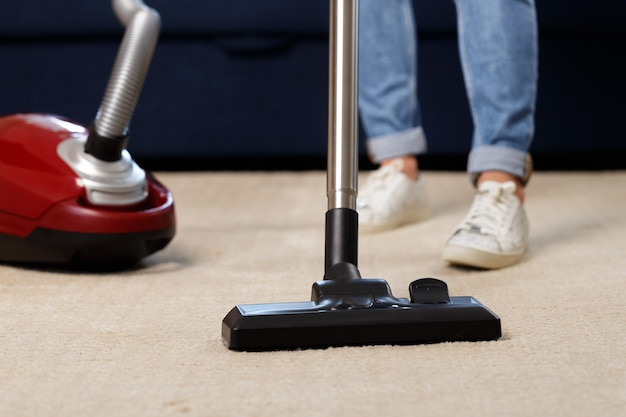 Close up of a woman vacuum-cleaning the carpet