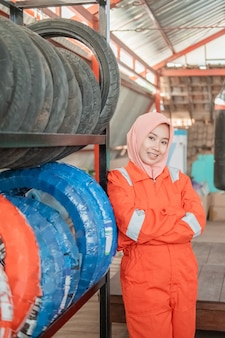 Close up of a woman in a veil wearing a wearpack uniform with crossed hands beside a tire rack in a motorcycle repair shop