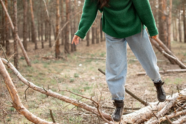 Close-up woman walking on fallen tree