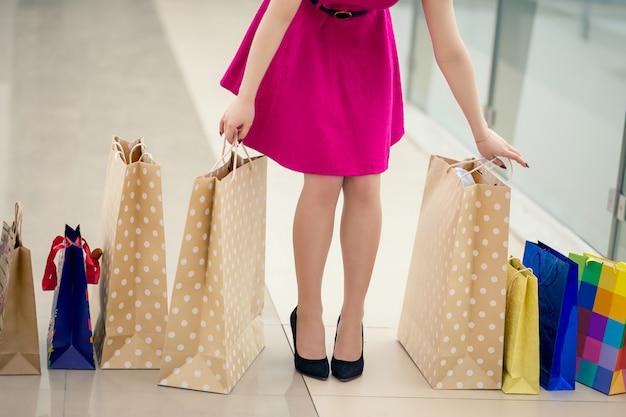買い物袋と一緒に歩いている女性を閉じる
