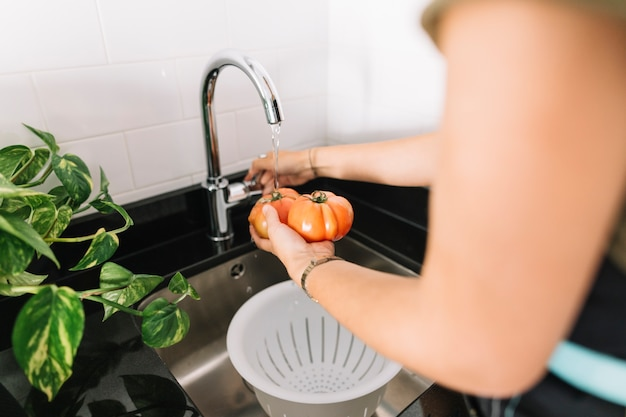 Close-up of woman washing fresh tomatoes in sink
