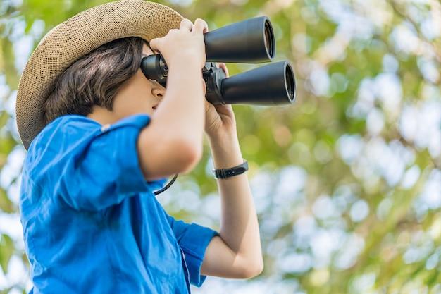 女性の帽子を閉じるし、芝生のフィールドで双眼鏡を保持