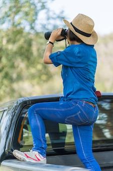 女性の帽子を着用を閉じるし、芝生のフィールドで双眼鏡を保持