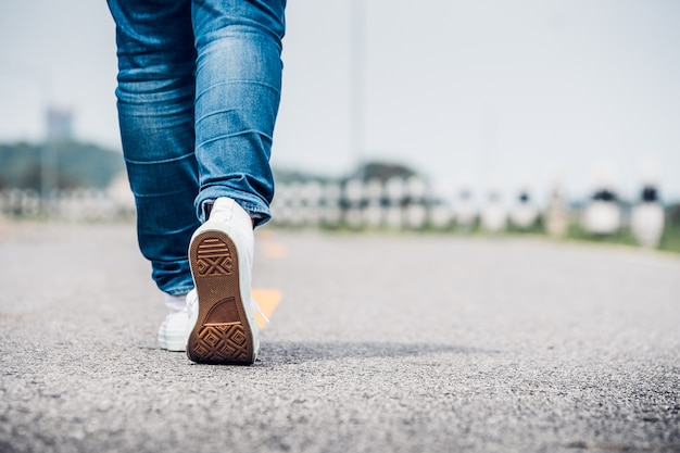 Close up woman wear jean and white sneaker walking forward on highway road in sunny day