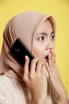 黄色の壁に隔離されたショックを受けた表情の携帯電話を使用してヒジャーブを身に着けている女性をクローズアップ