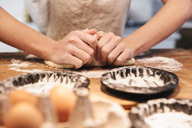 Close up of a woman wearing apron preparing dough for an apple pie at the kitchen at home