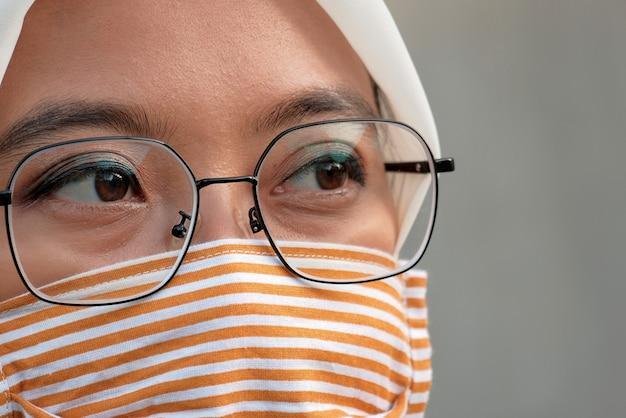 천으로 된 얼굴 마스크를 쓴 여자를 닫습니다
