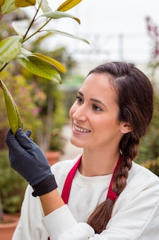 Close-up woman wearing gardening clothes and touching plants in greenhouse