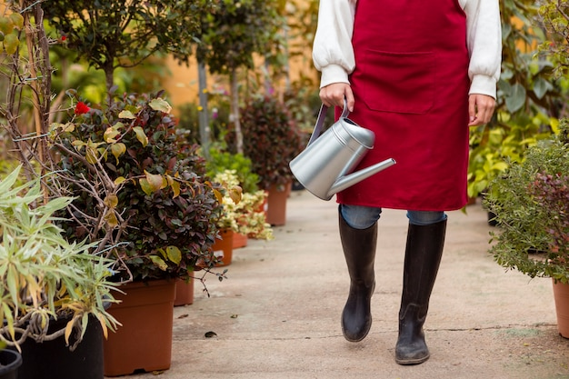 Close-up woman wearing gardening clothes walking in greenhouse