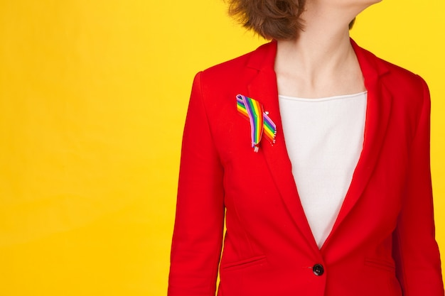 Close up of woman wearing gay pride awareness ribbon on her chest