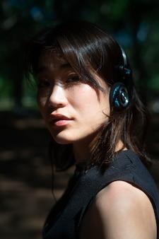 屋外でヘッドフォンを着用している女性をクローズアップ