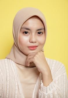 Крупным планом женщина в хиджабе улыбается, держа челюсть, глядя в камеру, изолированную на желтом фоне