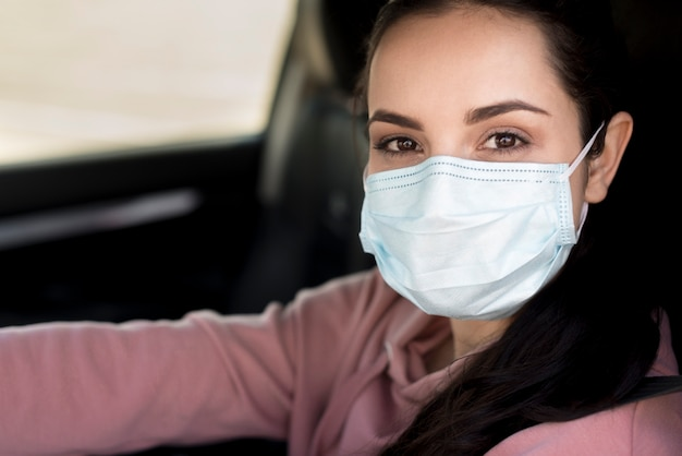 Close-up woman wearing mask inside her own car