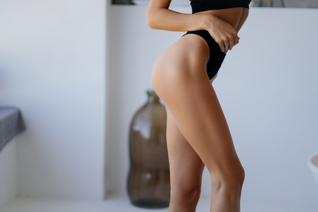 Close up of woman wearing panties in the living room.