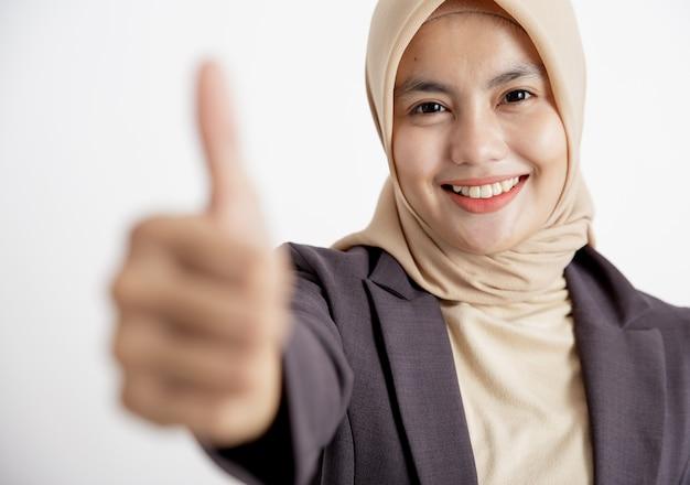 スーツを着ている女性をクローズアップヒジャーブ良いサインの手のポーズ、正式な孤立した白い壁