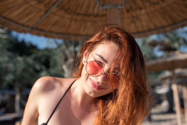 선글라스를 착용하는 여자를 닫습니다