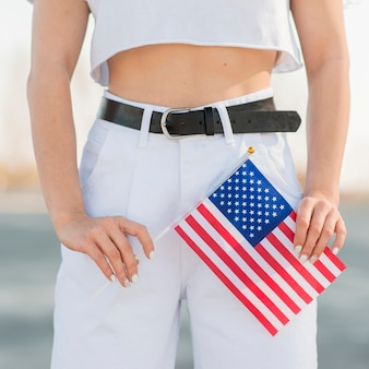 Close-up woman in white clothes holding usa flag in hands
