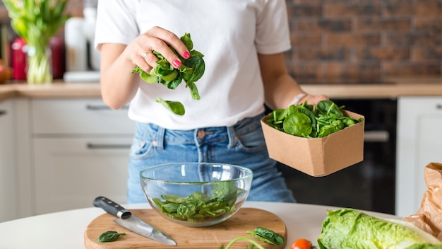 Close up woman in white t-shirt cooking salad with motion effect at home kitchen. process of cooking healthy food, vegetable salad concept. menu, recipe book banner