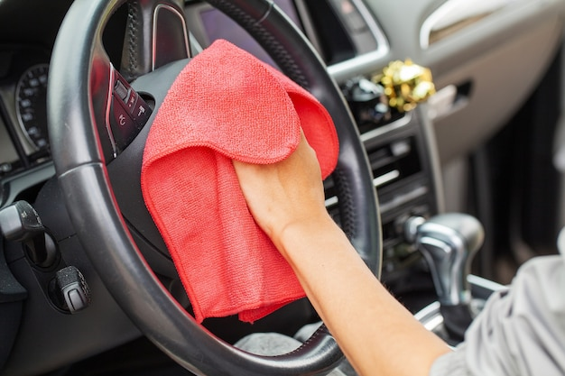 Close up of woman wiping car interior with red rag.