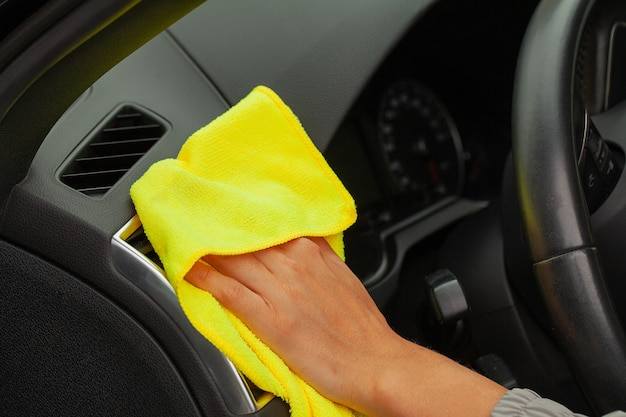 Close up of woman wiping car interior with yellow rag.