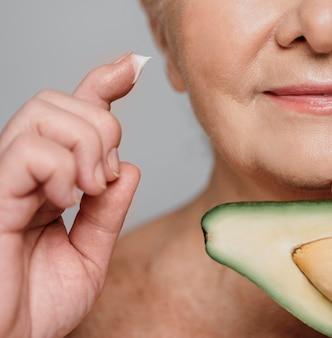 Крупным планом женщина с авокадо и сливками