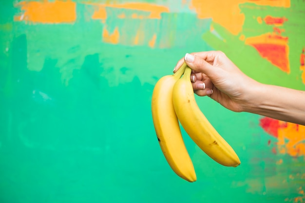 Close-up woman with bananas and colourful background