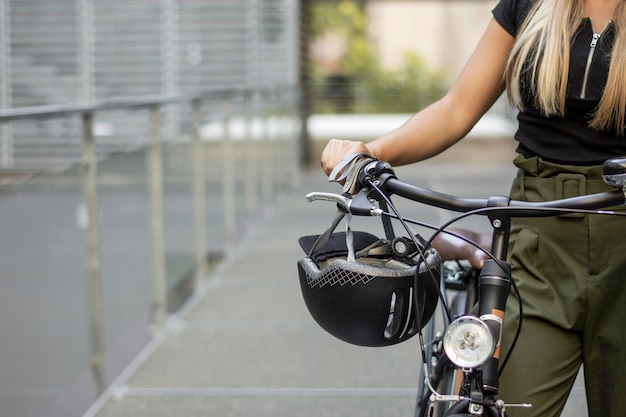 Крупным планом женщина с велосипедом и шлемом