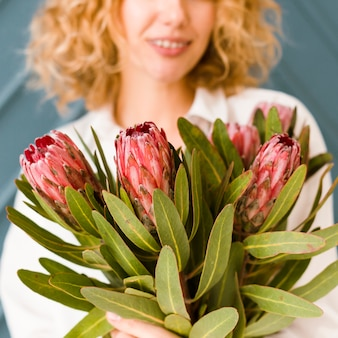 Close-up woman with bouquet smiling