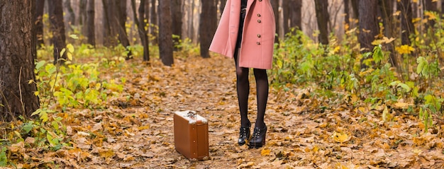 Close up of woman with brown retro suitcase walking through the