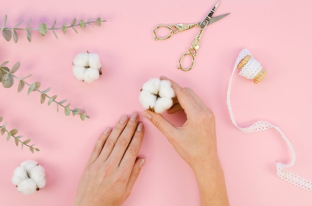 綿の花と葉を持つクローズアップ女性