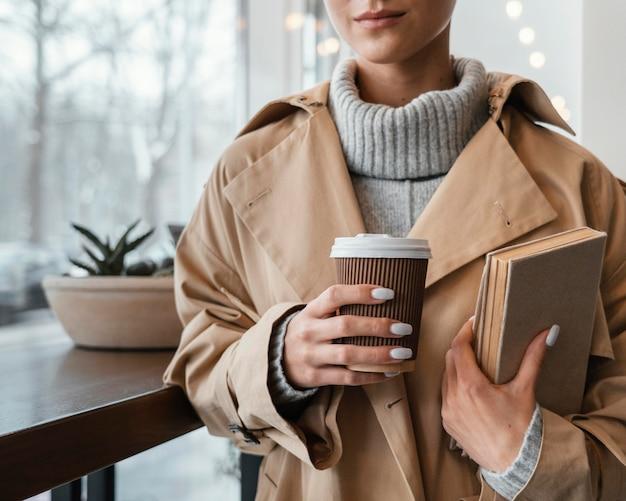 Крупным планом женщина с чашкой и книгами