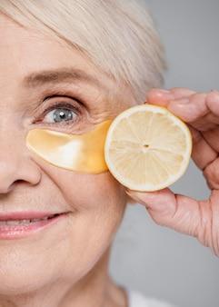Крупным планом женщина с повязкой на глазу и долькой лимона
